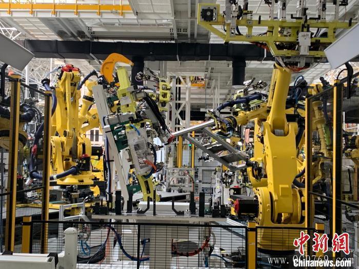 """在位于江西上饶的一家新能源电动汽车公司的智慧工厂内,412台宛如""""变形金刚""""的机器人正同时作业。 李韵涵 摄"""